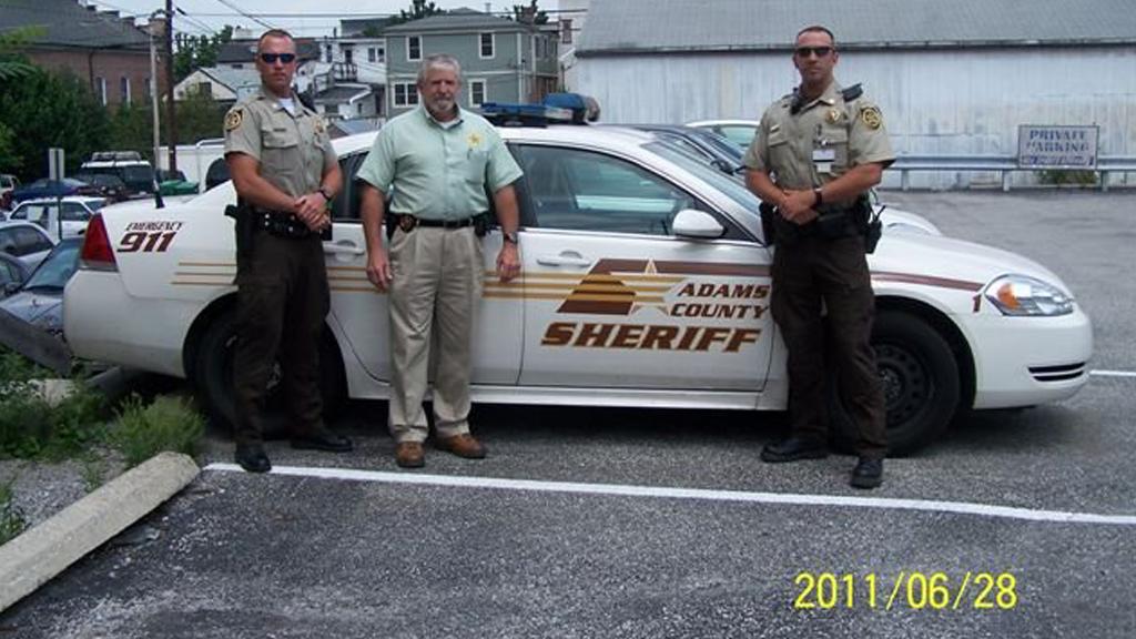 three sheriffman standing outside of adams sheriff car designed by gdi