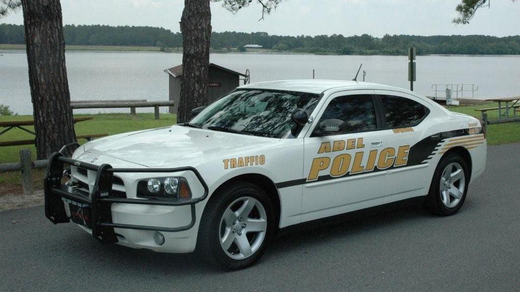 white adel police car parked near river