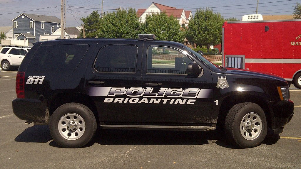 black brigantime police car with logo and white font color