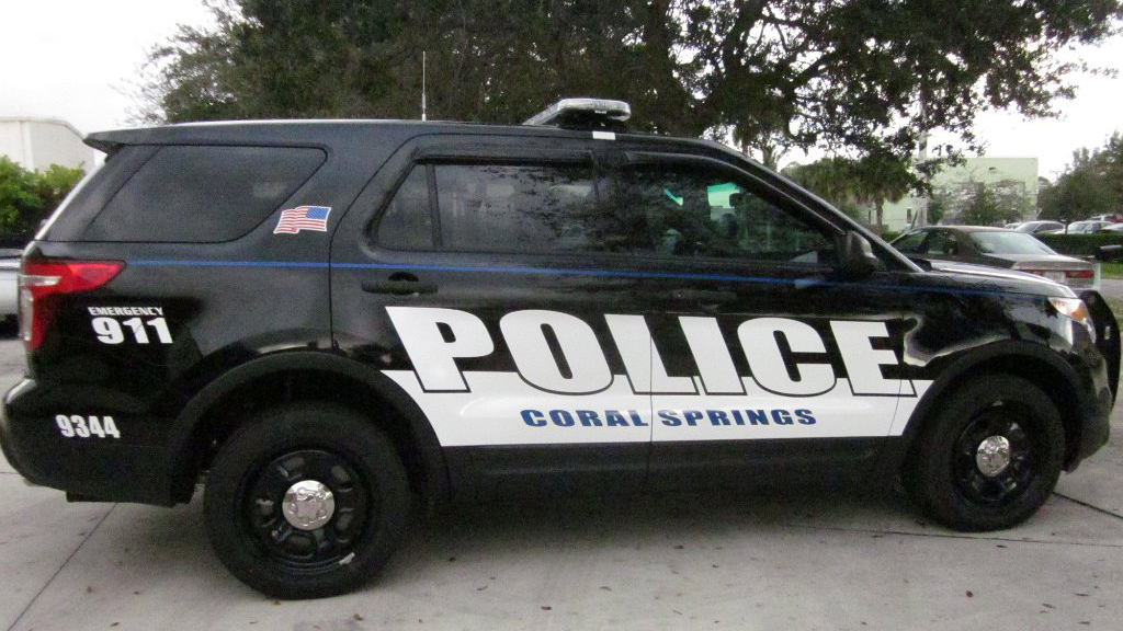 coral springs black police car parked near the tree