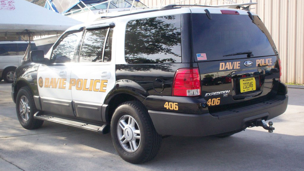 white and black davie police car with gold design