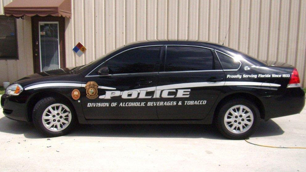 black police car with text of division of lacoholic beverages & tobacco and logo design