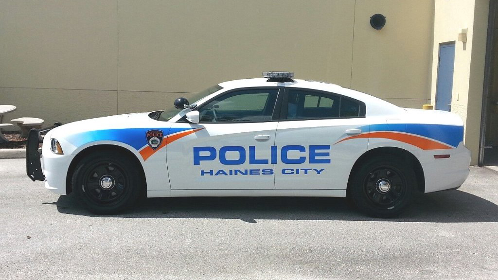 haines white police car with orange and blue line design parked near the building