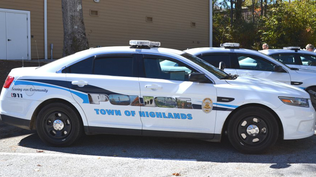 highlands white police car with nature font design parked near the building