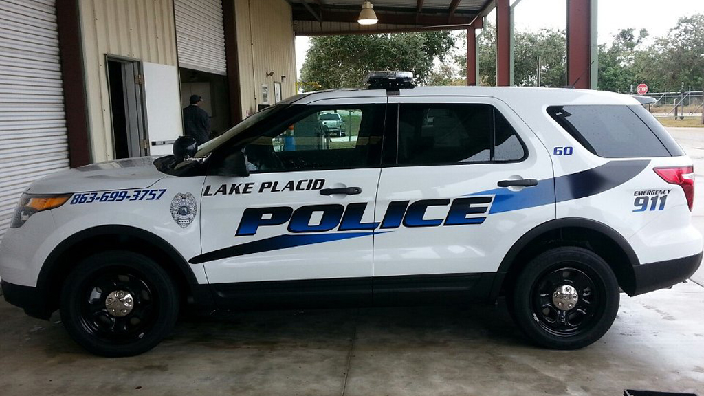 white lake placid police car with blue line design parked in the garage