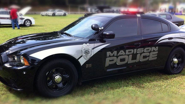 black madison police car with white line design parked in a field