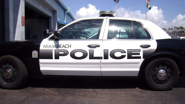 miami beach white police car parked in a field