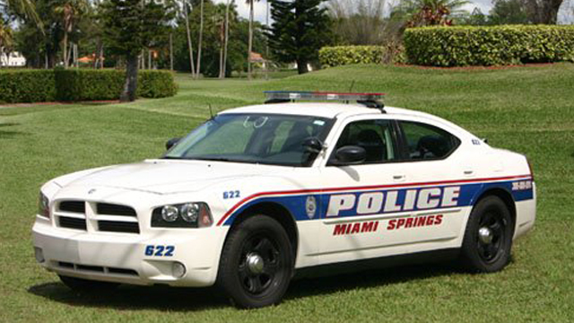miami springs white police car designed with blue and red lines parked in a grass field