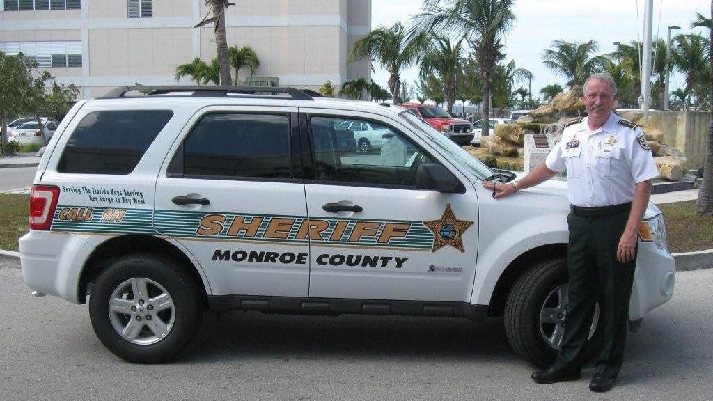 man standing outside the monroe white sheriff car