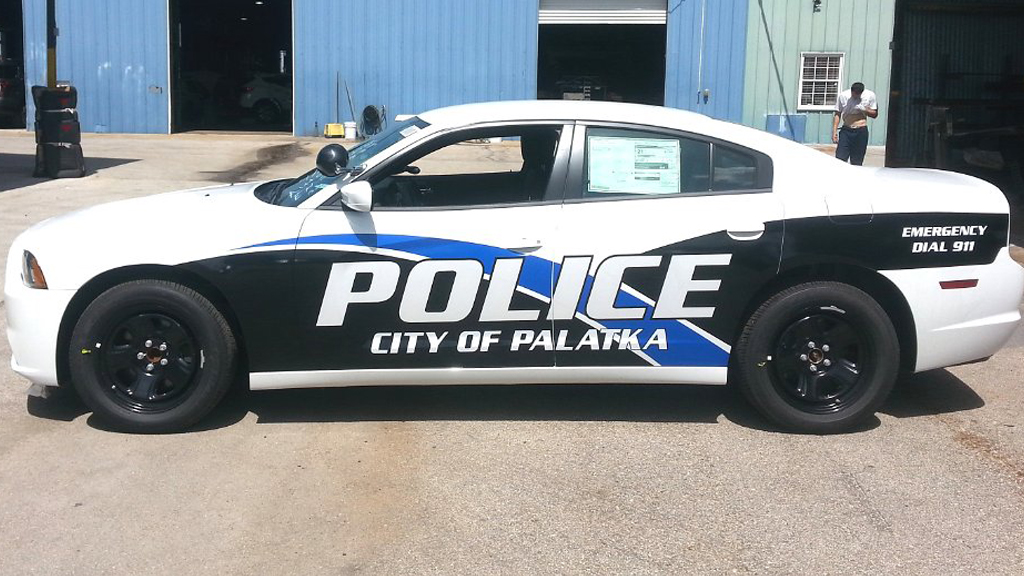 palatka white police car with blue and black line design parked near storage room