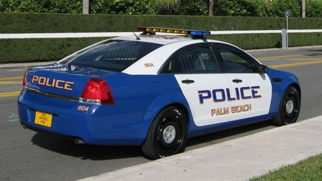 sideview of a white blue designed police car palm beach