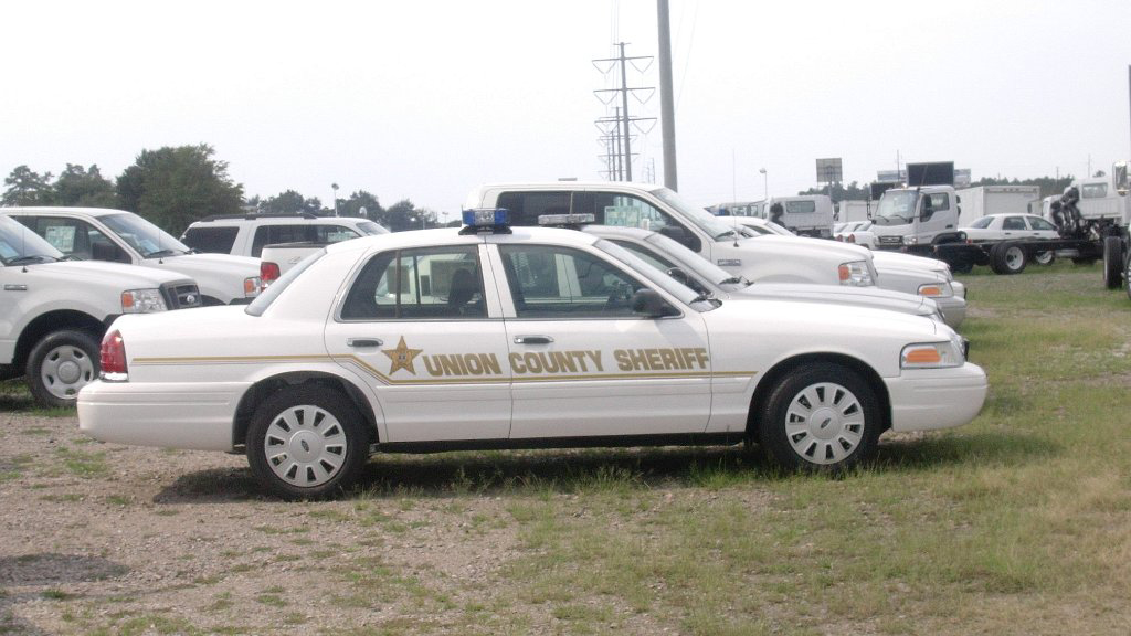 parked union sheriff white car in a field with gold design