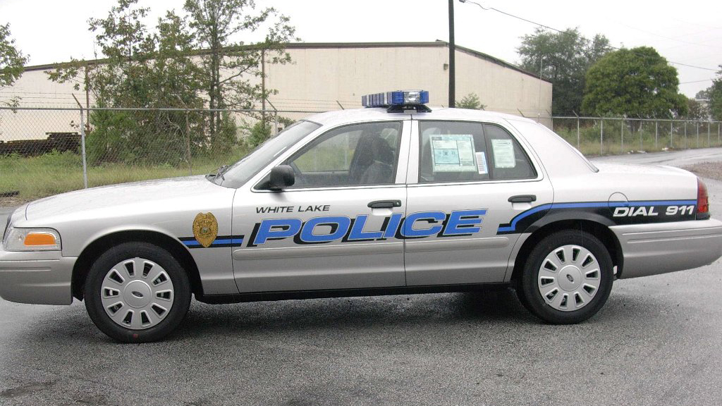 grey white lake police car with blue font and logo design parked in the street
